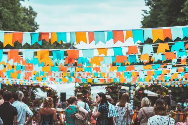 Around 30–50 strands of fabric bunting are tied across the main thorough-fair of an event. The sky is blue, the bunting is coloured cyan blue, and tangerine orange. The crowd below the bunting is dressed for summer and there are flowers on archways in the background.