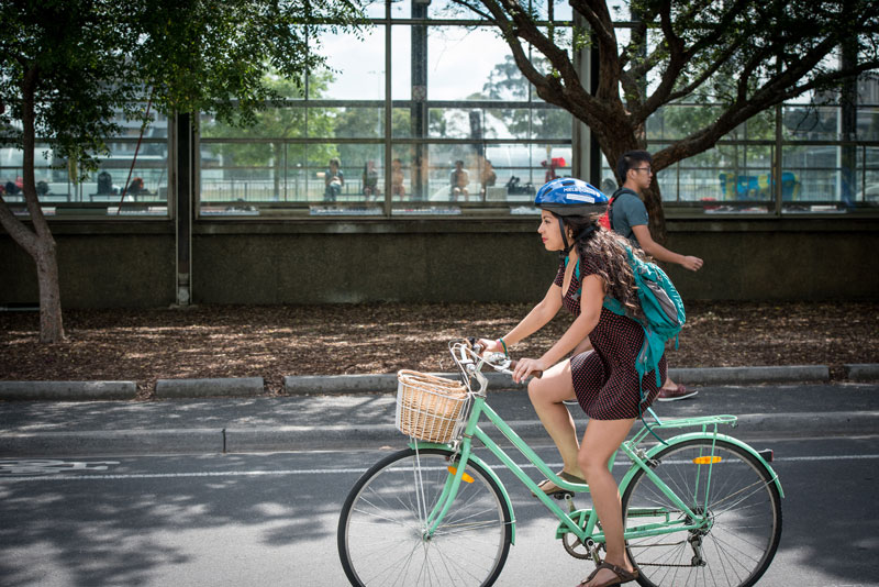 Student riding bicycle through campus