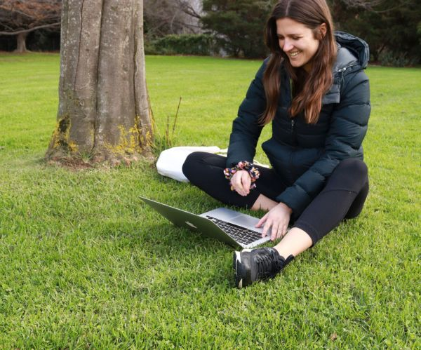 Student sitting on South Lawn with laptop
