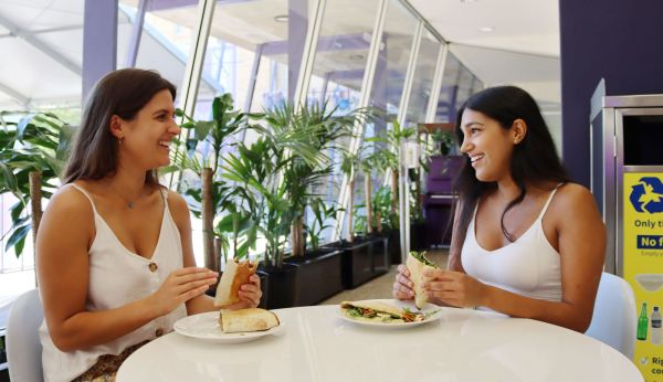 Two women talk while sitting across from each other at a white table. They each have a wrap in their hands, and their meal is on a ceramic plate.