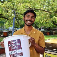 Photo of Hariz holding an organics bucket