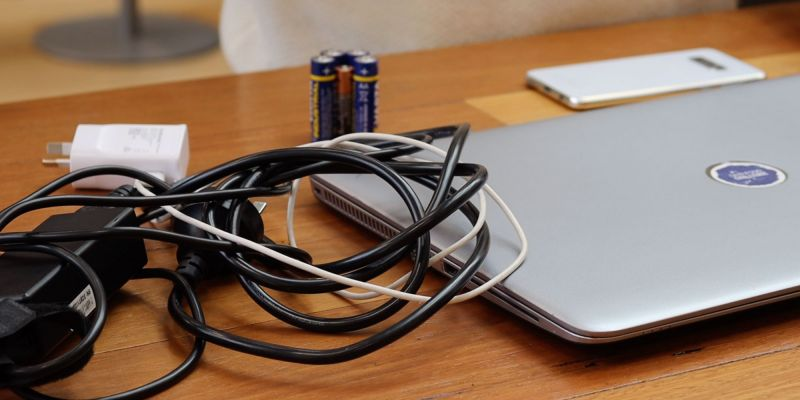 A silver laptop, white smart phone, group of double A batteries, and a bundle of cords placed on a wooden table