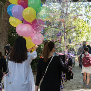 Two women walk with their backs towards the camera holding two big bunches of balloons. One holds a bunch of colourful balloon, one hold a bunch of clear balloons