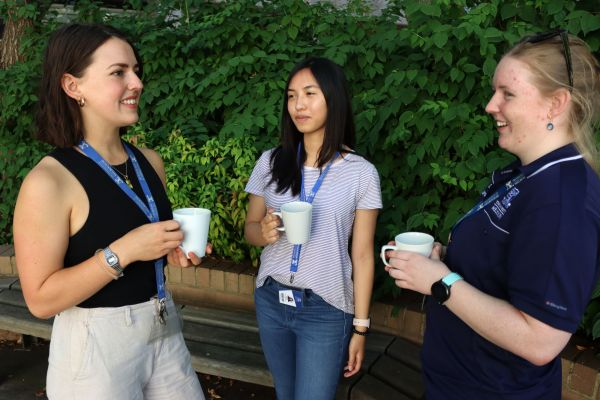 Three women wearing University of Melbourne Lanyards holding coffee mugs in in front of a bush